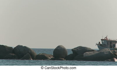 Rocks in the ocean and a boat