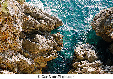 Rocks in the sea, waves hitting rocks.