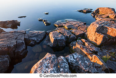Rocks of stony coast in calm water of lake