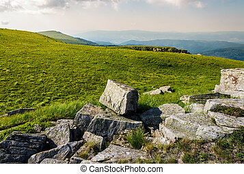 rocks on grassy meadow on top of a hill