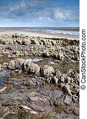 rocks on sandy beach and blue sky clouds