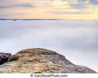 Rocks on the edge of a mountain. Foggy mountain valley