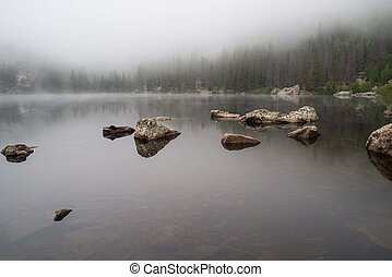 Rocks reflected in a foggy lake
