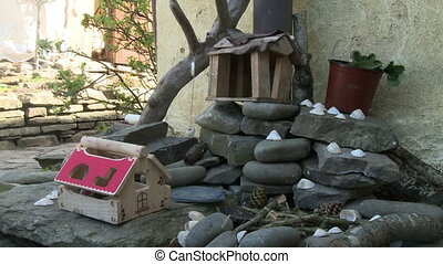 Rocks, shells, and boxes on the ground by a house - Piles of...