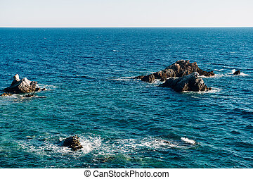 Black rocks stick out from the sea water. High quality photo