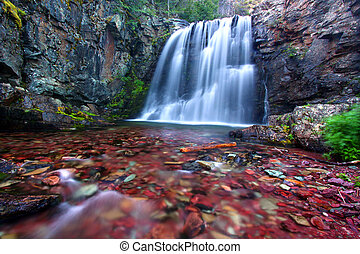 Bright stones shine through clear waters of Rockwell Falls in Glacier National Park.