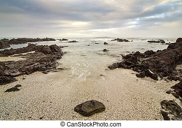 Rocky beach and clouds - Wide shot of a very rocky beack...