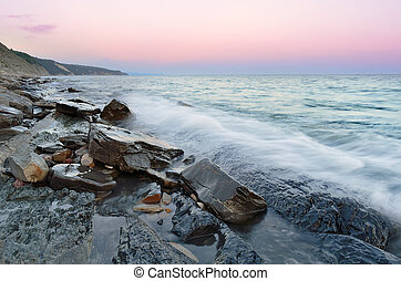rocky beach and sea waves under the