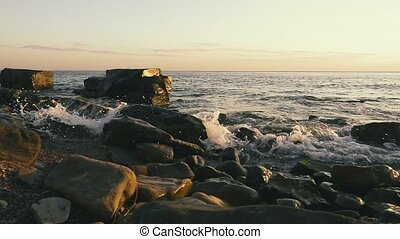 Rocky beach at sunset and clear sky slow mo