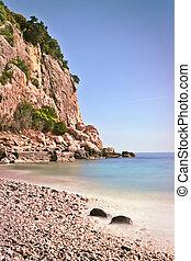 Rocky beach high cliffs blue sea