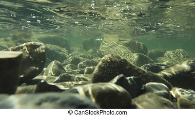 Rocky bottom and sunbeams under water slow motion