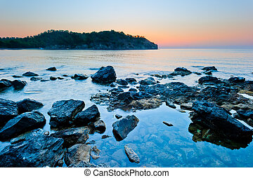 rocky bottom of the sea and the sunrise over the mountains