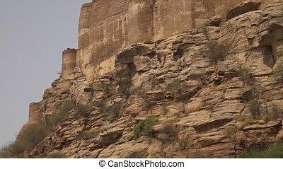 Rocky cliff below Mehrangarh Fort - Tilt up from a view of...