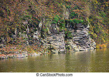 rocky cliff over the river in forest