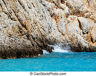 Rocky cliffs and amazing blue sea - wave crashing on the cliff