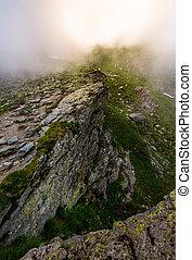 rocky cliffs of Fagaras mountains in fog. fantastic...