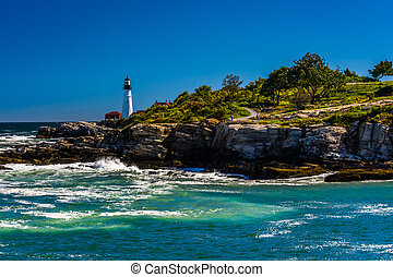 Rocky coast and view of Portland Head Light, at Fort Williams Park, Cape Elizabeth, Maine.