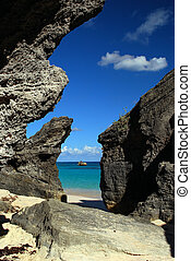 rocky coast - pink sand beach peeking through rocky cliff