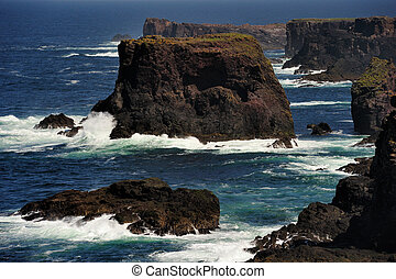Rocky coast with cliffs and splashing water at Esha Ness.