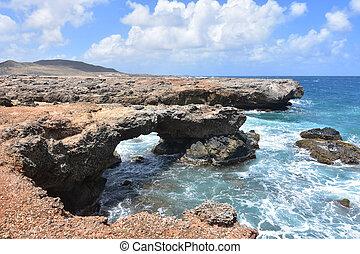 Pretty rock coastline on the shores of blear blue aruban waters