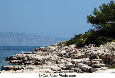 rocky coastline with sunbathers