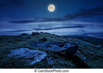 rocky formation on grassy hillside at night - rocky...