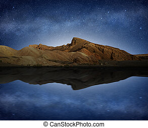 rocky hill reflected in water under a starry night sky