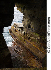 Eroded hole in sandstone cliffs in Orkney