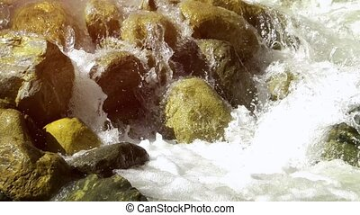 Continuous flow of a natural, mountain stream over rounded, algae encrusted boulders in this wilderness area in the Republic of Georgia. Ultra HD 4k stock footage with sound