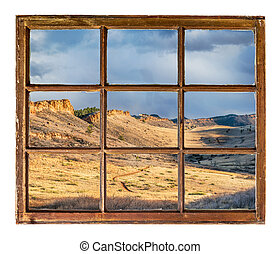 Rocky Mountains foothills in northern Colorado as seen through vintage, grunge, sash window with dirty glass