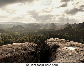 Rocky peak without people. View over wet sandstone rocky peak into forest landscape.
