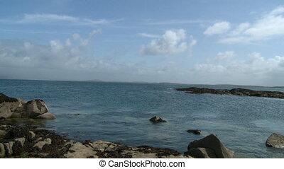 Rocky Peninsula Shoreline Of Sea - Steady, wide shot of a...
