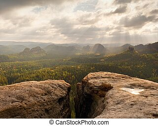 Rocky ppeak without people. View over wet sandstone rocky peak into forest valley, Sun hidden