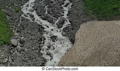 Rocky river and stones with the remains of mountain snow in...