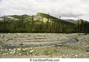 A view of a rocky river bed under a mountain peak in Alaska
