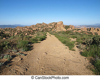 Rocky Road - A simple dirt road on a rocky mountain ridge in...