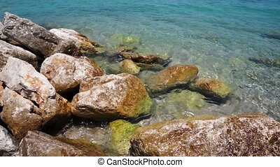 Rocky sea beach with clear water. - Rocky sea beach with...