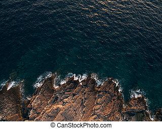 Rocky sea coast, waves hitting the rocks, aerial top view.
