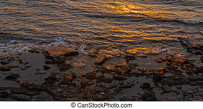 Rocky seashore and sun reflections at sunset in Pomos, Cyprus