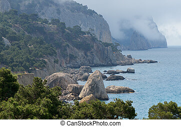 Seascape with a rocky shore. Clouds in the mountains above the sea. Crimea. Ukraine