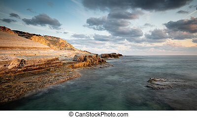 Rocky seashore seascape with dramatic and beautiful sunset at sea caves coastal area in Paphos, Cyprus