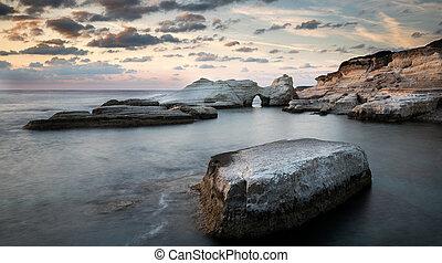 Rocky seashore seascape with wavy ocean at sea caves coastal area in Paphos, Cyprus