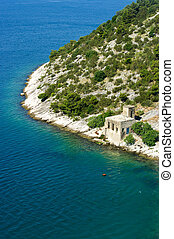 Rocky seashore with strange building in Croatia