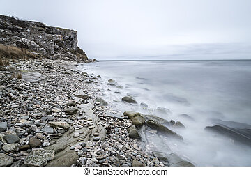 Rocky Shore by Ocean with cliff and a cloudy sky.