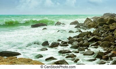 Rocky shore of a tropical sea in cloudy weather. Big waves