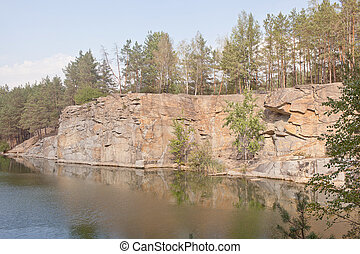 Rocky shore of the river, overgrown with forest