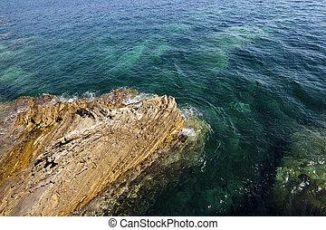 rocky shore   -   rocky shore into the sea. close up