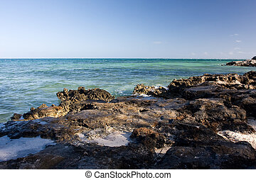 rocky shoreline with clear turquoise sea and ble sky
