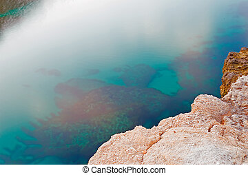 rocky shore and green water in Sardinia