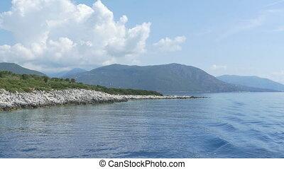 Rocky Shoreline behind Vessel - Cruising near the sea...